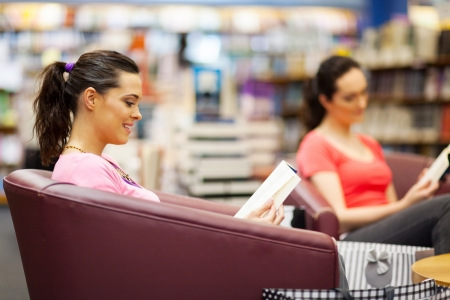 young woman reading book in bookstore Stock Photo - 15401496