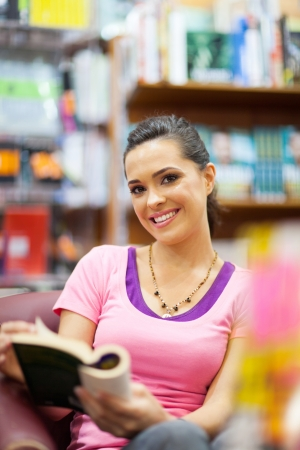book shop: young woman reading a book in library