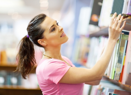 young woman searching for a book in bookstore photo