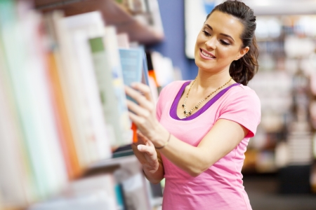 book shop: young woman choosing a book in bookstore Stock Photo