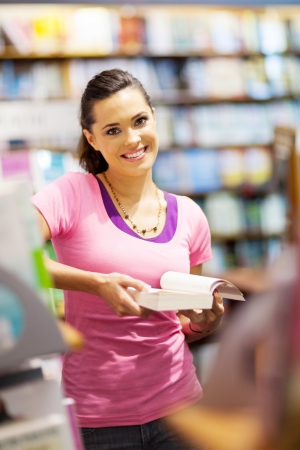 causal clothing: pretty female college student reading a book in library  Stock Photo