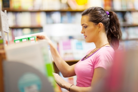 young woman choosing a book in bookstore or library  photo