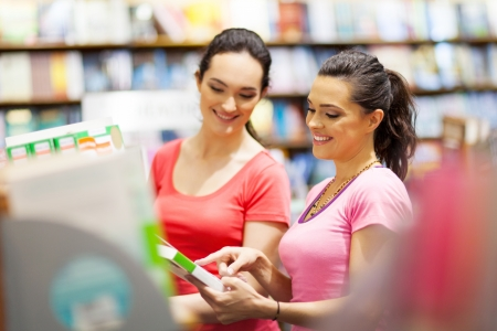 book shop: two young woman choosing a book in bookstore or library Stock Photo
