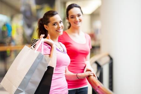 faire les courses: deux jeunes femmes faire du shopping dans un centre commercial