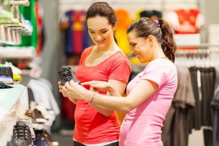 shoe store: mujeres jóvenes la compra de zapatos deportivos