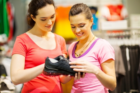 customer assistant: shop assistant helping customer choosing sports shoes