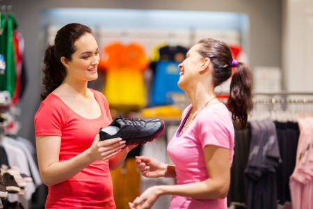 saleswomen: shop assistant helping customer choosing sports shoes