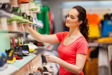 tienda zapatos: ropa deportiva femenina joven dependienta de trabajo en la tienda Foto de archivo