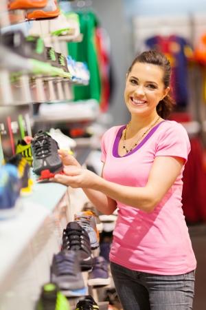comprando zapatos: mujer joven feliz elección de los zapatos deportivos para comprar en la tienda