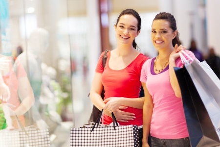 friends shopping: two happy friends shopping in mall Stock Photo