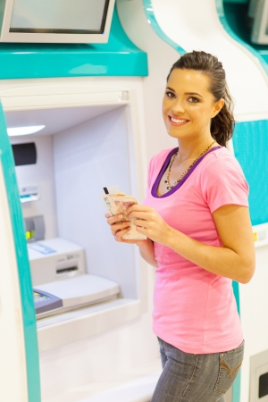 withdraw: happy young woman withdrawing cash at an ATM Stock Photo