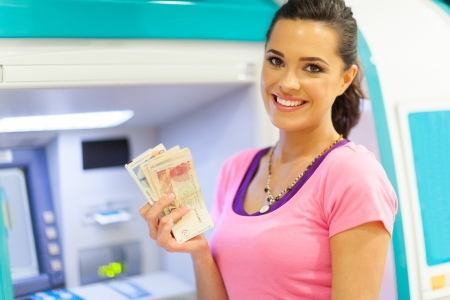 happy young woman withdrawing or depositing cash at an ATM photo