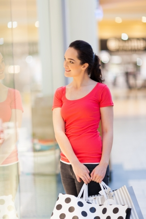 young woman with shopping bags looking at store showcase Stock Photo - 15402218