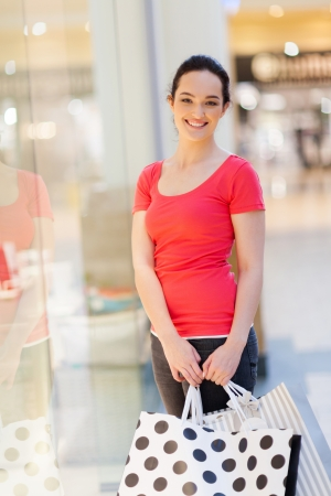 happy woman with shopping bags in mall photo