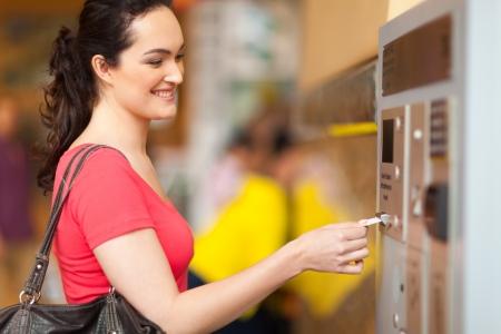 parking facilities: mujer joven pagar por el aparcamiento en la estaci�n de pago