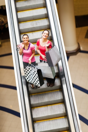 happy shopping women on escalator with shopping bags photo