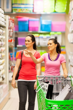 hypermarket: two young women walking in supermarket with trolley Stock Photo