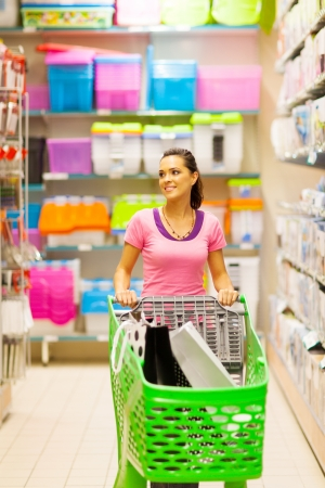 young woman walking in supermarket aisle with trolley photo