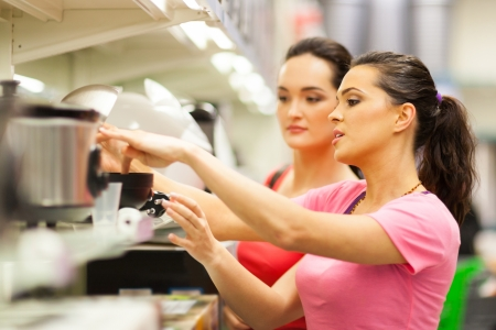 young women shopping for appliance in supermarket photo