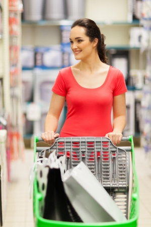 happy young woman pushing a trolley in supermarket Stock Photo - 15402201