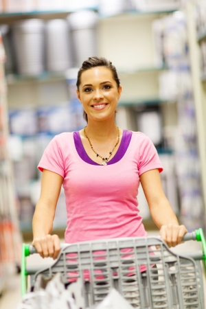 happy young woman pushing trolley in supermarket photo