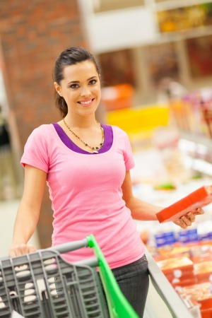 carro supermercado: felices compras mujer joven para los alimentos congelados en el supermercado