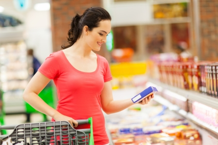 happy shopper: young woman doing grocery shopping in supermarket Stock Photo