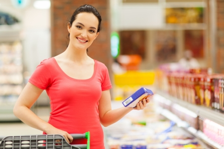 frozen food: happy young woman shopping for frozen food in supermarket Stock Photo