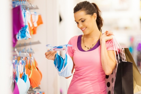 attractive young woman shopping for underwear in clothing store photo