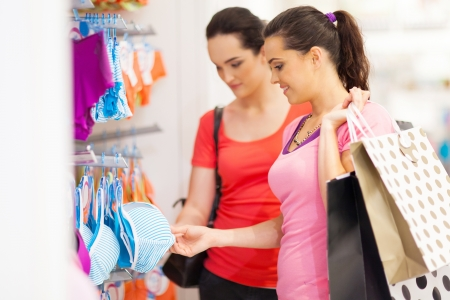two young woman shopping for lingerie in clothing store photo