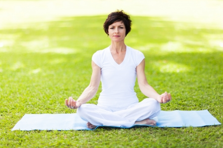 elegant middle aged woman doing yoga meditation Imagens