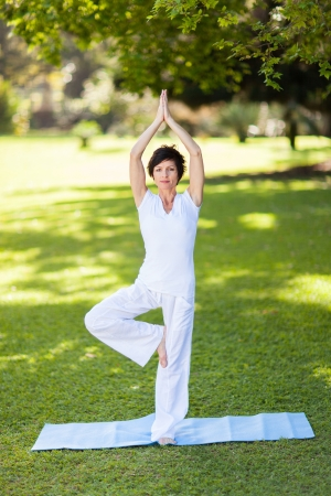 beautiful middle aged woman: beautiful middle aged woman doing yoga outdoors