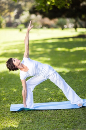 healthy middle aged woman stretching outdoors photo