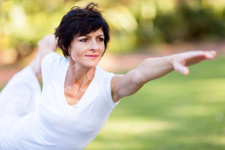 middle aged: healthy middle aged woman stretching outdoors Stock Photo