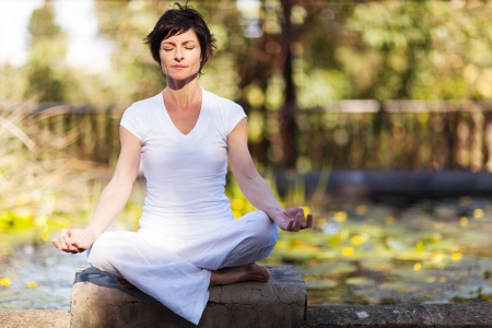 middle aged woman doing yoga meditation outdoors Stock Photo