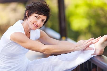 beautiful middle aged woman: beautiful middle aged woman stretching leg Stock Photo