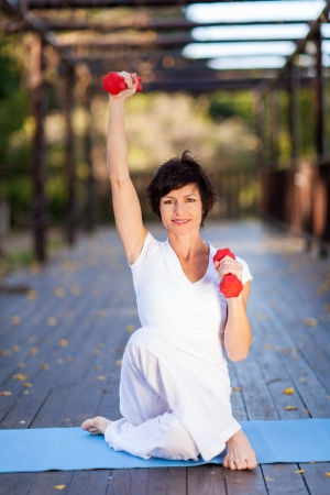 beautiful middle aged woman: beautiful middle aged woman exercise with dumbbells Stock Photo