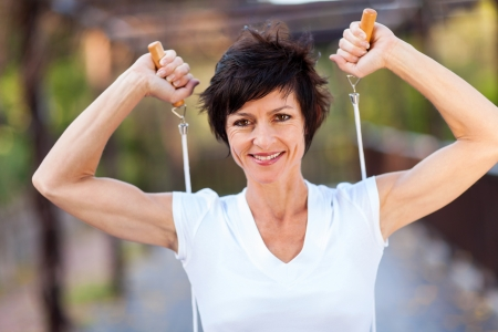 happy middle aged woman workout with jumping rope photo