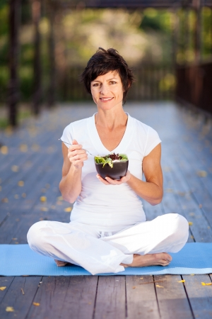 eating in the garden: healthy middle aged woman eating salad outdoors Stock Photo