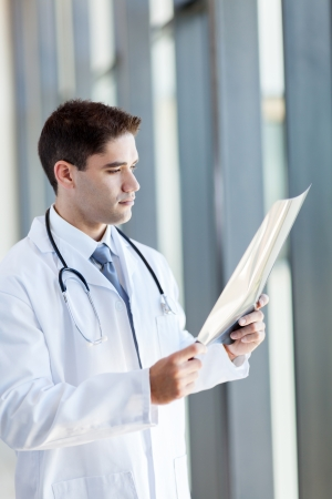 medical study: thoughtful doctor looking at patients x-ray film