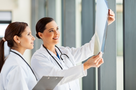 two female medical workers looking at patients x-ray film photo