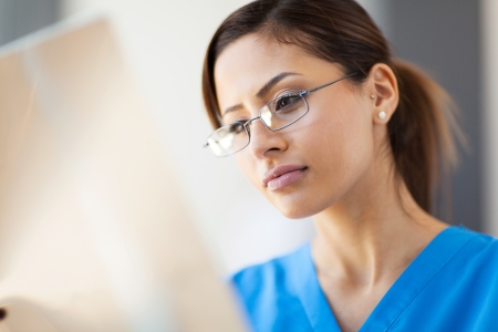 healthcare office: young pretty medical worker looking at x-ray film