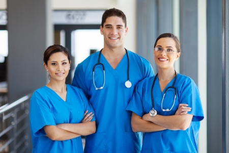 bushes: group of young hospital workers in scrubs Stock Photo