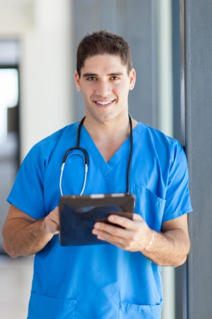 male medical doctor using tablet computer in hospital photo