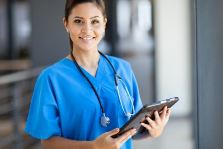 beautiful young female medical intern with tablet computer in office photo