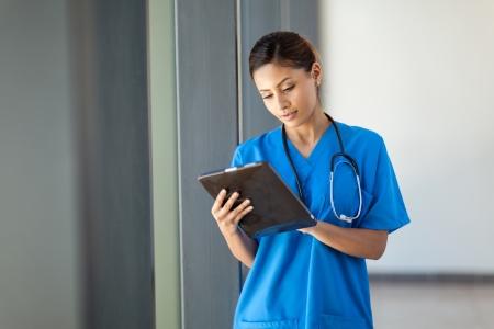 enfermeras: joven enfermera m�dico con equipo Tablet PC en la oficina del hospital