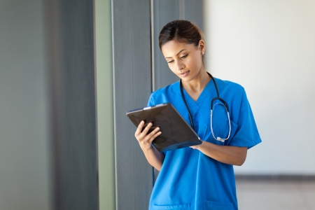 health care: young female medical nurse using tablet computer in hospital office