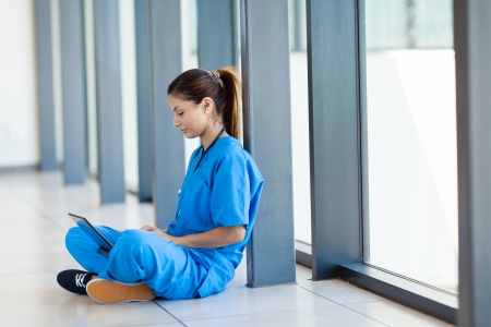 pretty nurse sitting on floor and using laptop computer during break photo
