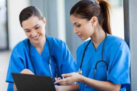 enfermeros: dos trabajadores de la salud hermosas mujeres usando la computadora port�til Foto de archivo