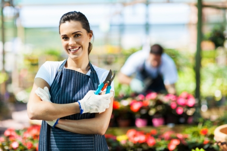 small business owner: pretty female nursery worker portrait with pruner